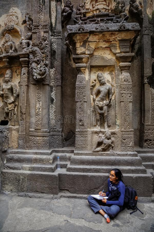 Ellora, Maharashtra, INDIA - JANUARY 15, 2018: Girl student makes a drawing while in the Kailash Temple. Standalone, multi-storeyed temple complex stock images
