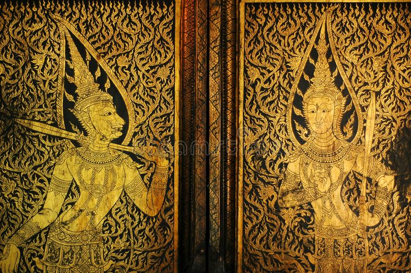 Golden antique drawing of Thai guardian angels on temple door. Double Golden antique drawing of Thai guardian angels on temple door vintage style royalty free stock photo