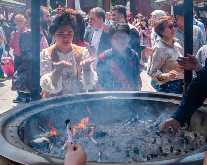 Tourists At Sensoji Temple Incense Burner, Tokyo, Japan. Tokyo, Japan - April 28th, 2017. Tourist drawing smoke believe to have healing properties from Jokoro or stock photography