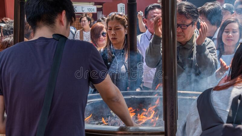 Tourists At Sensoji Temple Incense Burner, Tokyo, Japan. Tokyo, Japan - April 28th, 2017. Tourist drawing smoke believe to have healing properties from Jokoro or royalty free stock images