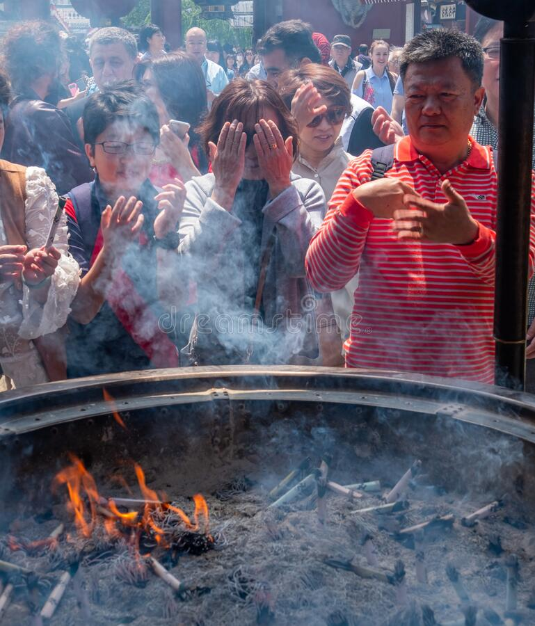 Tourists At Sensoji Temple Incense Burner, Tokyo, Japan. Tokyo, Japan - April 28th, 2017. Tourist drawing smoke believe to have healing properties from Jokoro or royalty free stock photos