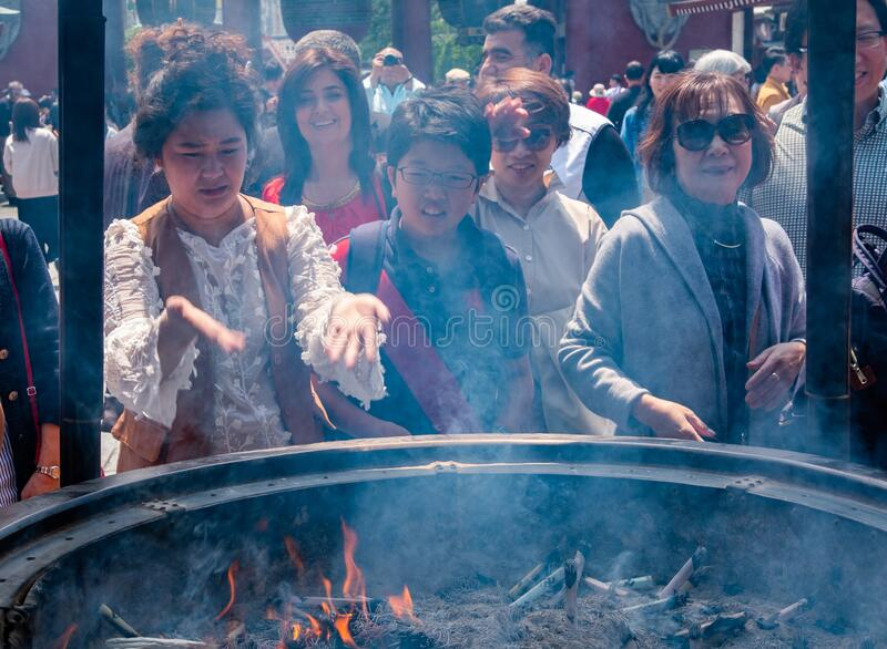Tourists At Sensoji Temple Incense Burner, Tokyo, Japan. Tokyo, Japan - April 28th, 2017. Tourist drawing smoke believe to have healing properties from Jokoro or stock image