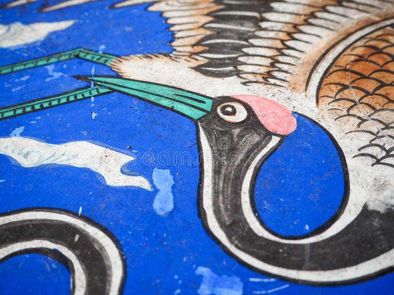 Wooden roof panel in a Chinese temple with a drawing of a crane. On a blue background stock image