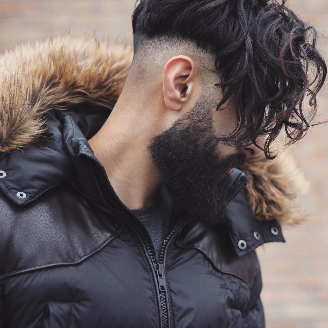 Long curly fringe undercut hairstyle for men